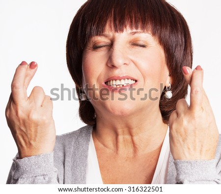 Mature woman with crossed fingers. Female showing a gesture with hands. Luck, wish - stock photo