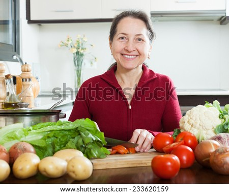 Mature woman with cutting tomato in home kitchen - stock photo
