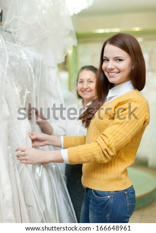 Mature woman  with daughter chooses white gown at shop of wedding fashion - stock photo