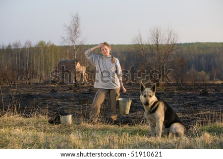 Mature woman with dog and bucket standing at sunset at burned field after extinguish fire. Country house at background.