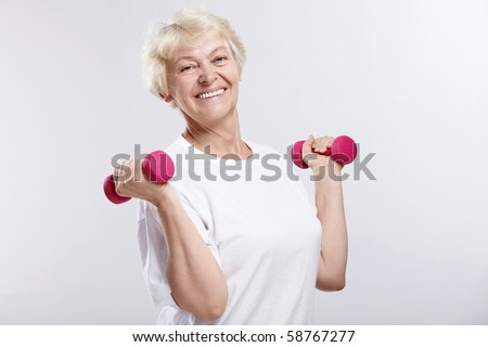 Mature woman with dumbbells on white background