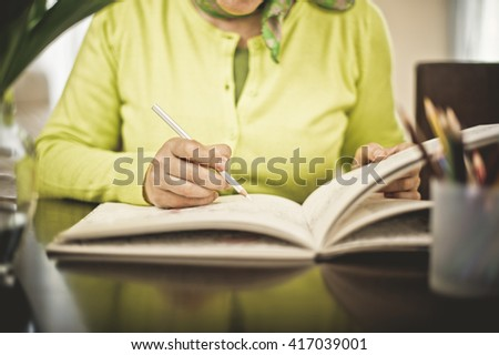 Mature Woman with Eyeglasses Coloring, Domestic life - stock photo