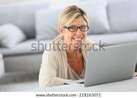 Mature woman with eyeglasses websurfing on laptop - stock photo