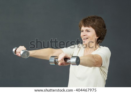 Mature woman with fitness dumbbells. Old woman is smiling in the studio. Mellow woman do her exercises and smile.  - stock photo