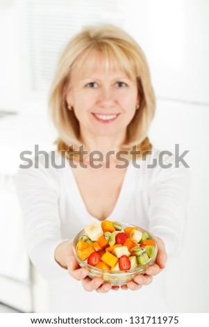Mature Woman with fruit salad in hand. - stock photo