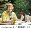 Mature woman  with  glass of red wine at outdoor restoraint - stock photo