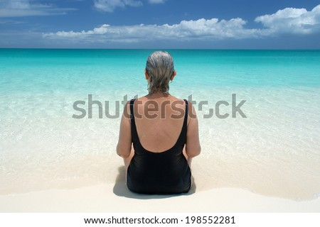 mature woman with gray hair sits at water's edge and looks out on ocean; back view with symmetry - stock photo