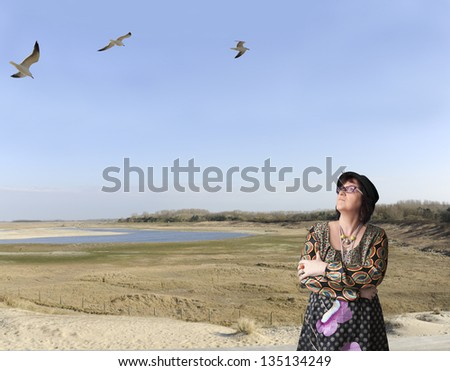 mature woman with hat outdoors, looking up at seagulls , location, zwin, knokke, belgium - stock photo