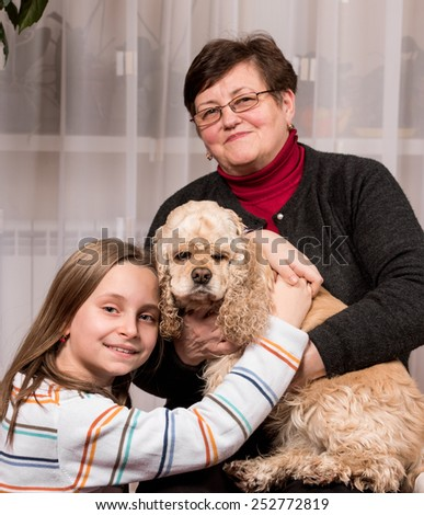 Mature woman with her granddaughter and a dog (american spaniel) at home