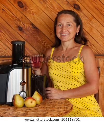 Mature woman with juicer machine - stock photo