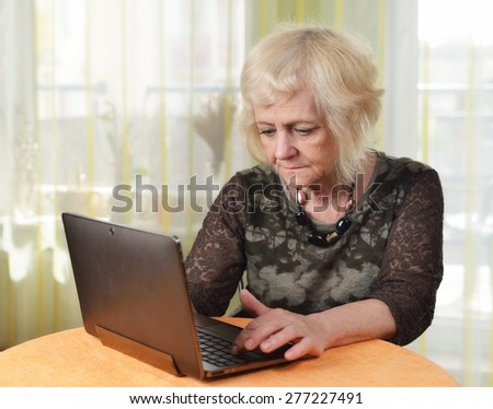 Mature woman with laptop in her room. MANY OTHER PHOTOS FROM THIS SERIES IN MY PORTFOLIO.