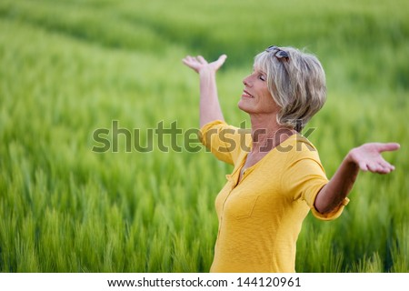 mature woman with outstretched arms in nature - stock photo