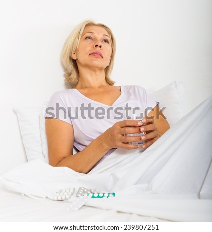 mature woman with pills and vitamins - stock photo