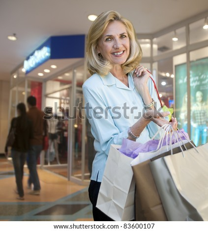 Mature woman with shopping bags at shopping center - stock photo