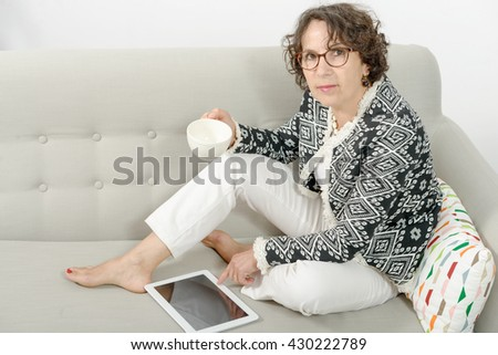 mature woman with tablet, drinking tea on the sofa