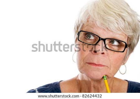 Mature woman with white hair and glasses looking up with a pencil under her chin. - stock photo