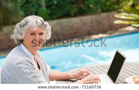 Mature woman working on her laptop - stock photo