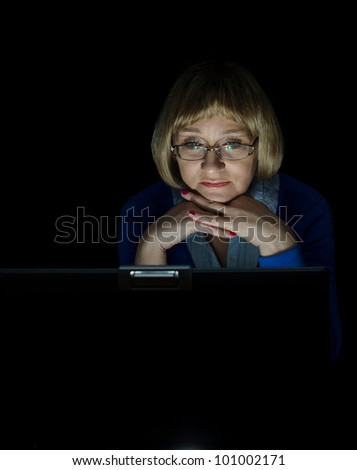 Mature woman working on laptop computer in night - stock photo