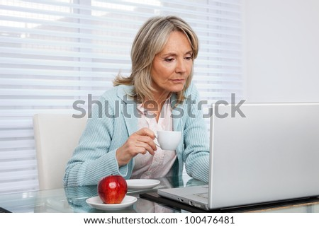 Mature woman working on laptop while holding cup of tea - stock photo