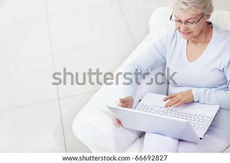 Mature woman working with laptop - stock photo