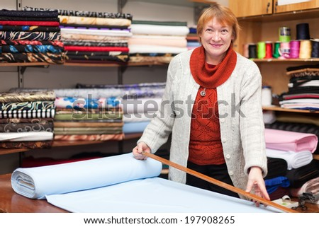 Mature woman  works at  fabric store - stock photo