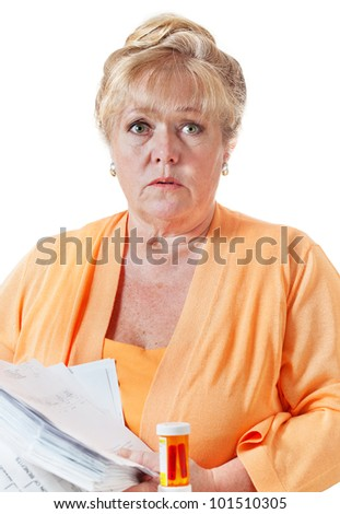 Mature woman worried about the large pile of health insurance forms and claims paperwork - stock photo