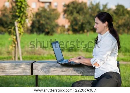 Mature woman writing on laptop sitting on the wooden table in the park