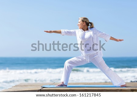 mature woman yoga exercise on beach  - stock photo