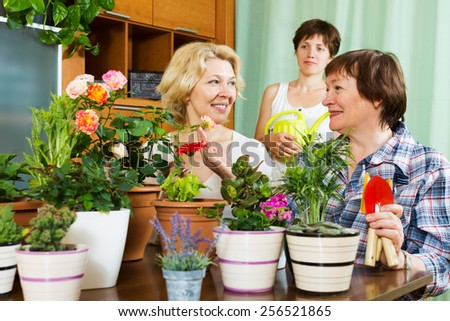 mature women  and girl near table with many flowerpots - stock photo