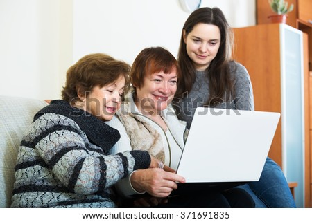 Mature women and happy girl with laptop at home - stock photo