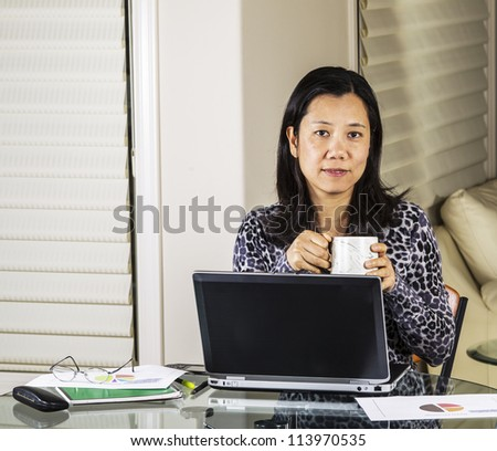 Mature women drinking coffee while working from home office - stock photo