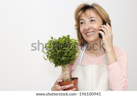 Mature women florist  taking orders by phone.  - stock photo