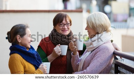 Mature women in warm clothes having cup of hot tea on terrace - stock photo