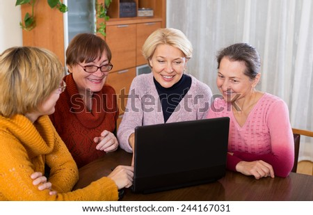 Mature women making accounts on date site at home - stock photo
