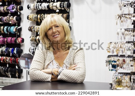 Mature women owner with arms crossed smiling at looking at camera. - stock photo