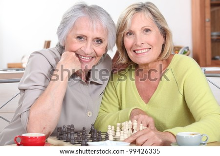 mature women playing chess - stock photo