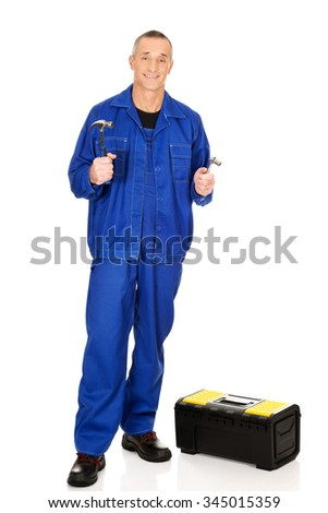 Mature worker with toolbox showing his wrench and hammer.