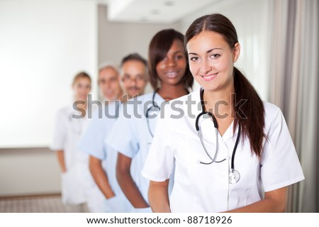 Mature young female doctor with group of happy successful colleagues - stock photo