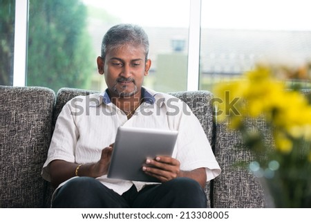 matured indian male with a tablet on a sofa setting - stock photo