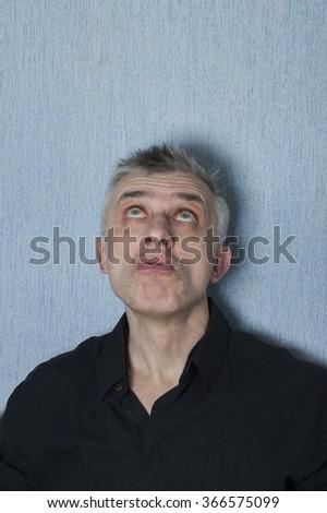 Matured man in black shirt looking thoughtfully up, vertical studio shot - stock photo