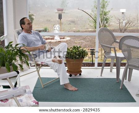 Maturer man in bare feet enjoys his morning coffee in screened porch - spring in Florida. - stock photo