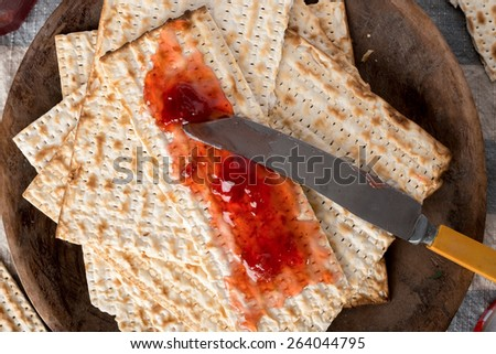 Matzah, served here with strawberry preserves,  the unleavened bread used in the Jewish holiday passover, set on wood bowl in rustic setting - stock photo