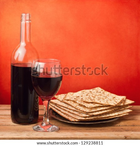 Matzo and wine for passover seder celebration on wooden table over red background - stock photo
