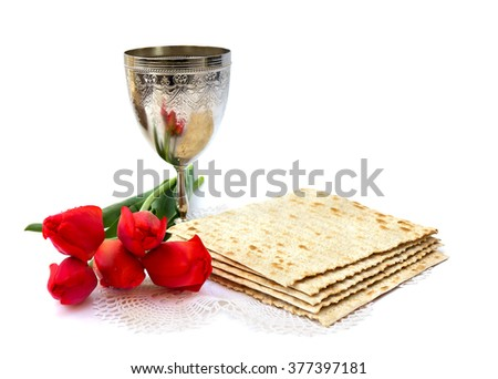 Matzo, wine and red tulips for passover celebration on white background. - stock photo