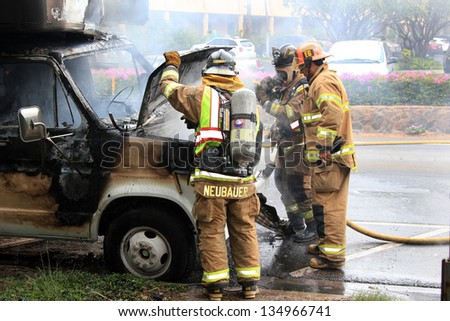 MAUI, HAWAII-APR 12: Firemen responding to a vehicle fire of unknown origin on April 12, 2013 in Maui, Hawaii. The cab and engine compartment were fully engulfed by the fire.