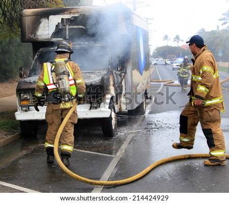 MAUI, HAWAII-April 12: Two firemen actively battling an automotive fire on a city street. Cause of the blaze is unknown, on April 12, 2013. For editorial use.
