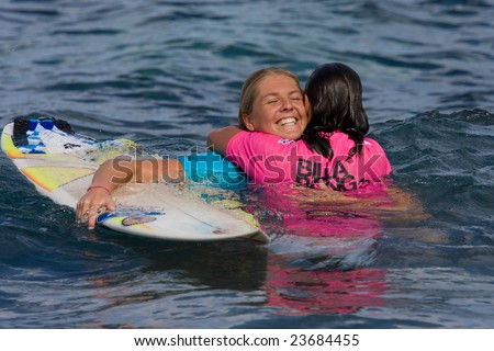 MAUI, HAWAII - DECEMBER 18, 2008:     Professional surfer Stephanie Gilmore hugs Layne Beachley after their heat during the Billabong Pro Maui - December 18, 2008 Maui, HI. - stock photo