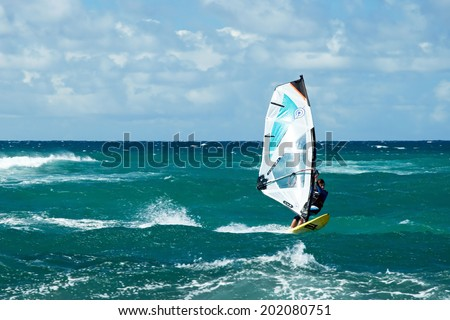 MAUI, HAWAII - SEPTEMBER 17, 2011 - Windsurfer in windy weather on September 15, 2011 in Maui, Hawaii. Windsurfing is a surface water sport that combines elements of surfing and sailing - stock photo