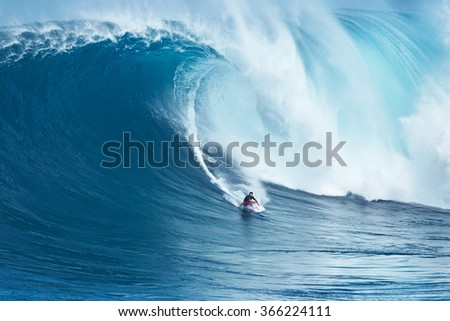 """MAUI, HI - JANUARY 16 2016: Professional surfer Francisco Porcella rides a giant wave at the legendary big wave surf break known as """"Jaws"""" on one the largest swells of the year. - stock photo"""