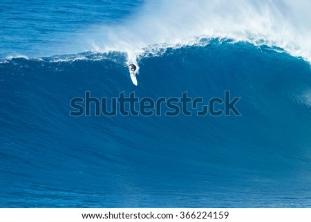 """MAUI, HI - JANUARY 16 2016: Professional surfer Ian Walsh rides a giant wave at the legendary big wave surf break known as """"Jaws"""" on one the largest swells of the year. - stock photo"""